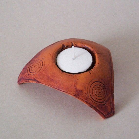 This is a rustic clay candle holder adorned with three spiral motifs. It has a triangular shape and a dynamic look. Theres also a round space in the middle for a small tea light candle. The measurements of this ceramic piece are: 1.3x4.3x4.3 (3,5x11x11 cm).  Ive used natural pigments to give the candle holder a special patina. This candle holder can also function as a ring holder. I also make other designs of ceramic candle holders, which you can see here…