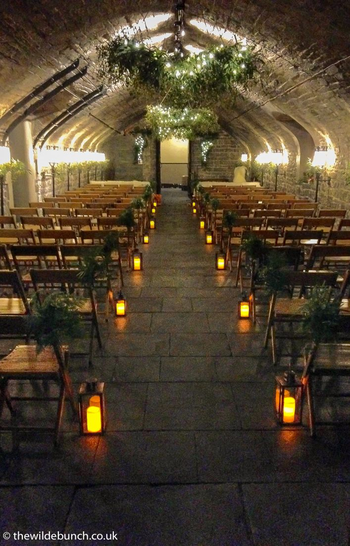 The undercroft at Cardiff Castle ready for the wedding ceremony of Alex Jones and Charlie Thomson. The ceilings were a cascade of mistletoe. All floral designs by The Wilde Bunch