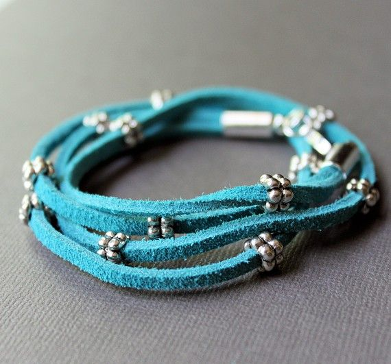 "Two strands of super soft, bright turquoise blue leather suede cord are doubled over to form a four strand wrap bracelet. The suede cord is decorated with pewter ""daisy"" beads for added detail; beads are secure but can moved if desired. It's finished with shiny silver plated end caps and a lobster clasp (last image shows variation in brown).    • This bracelet will be made especially for you. Please leave your wrist circumference in ""message to seller"" for a proper fit.  • Leather suede is…"
