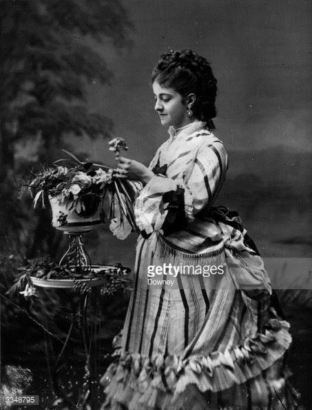 Excellent example of early bustle style.  Great hair, too!  News Photo : Anglo-Italian soprano Adelina Patti , arranging...