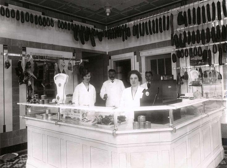 Interieur van modelslagerij van Hendrik Pasman in Steenwijk, met twee vrouwen en twee mannen in witte jassen achter de toonbank met kassa en weegschaal erop. Aan het plafond vele worsten. Nederland, 1929.