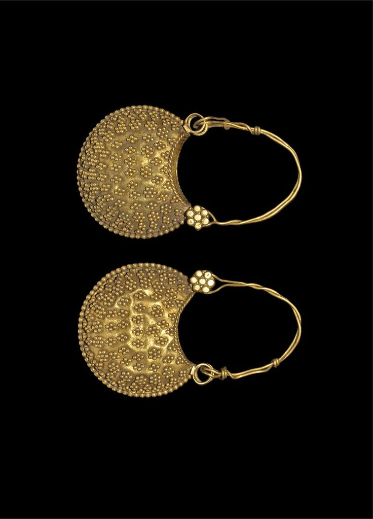 BYZANTINE GOLD EARRINGS Circa 10th-12th century AD. A pair of gold lunate earrings each with a twisted wire loop and floral stud pin supporting a hollow bifid crescent pendant with granule decoration in lines, lozenges and flowers. Gold