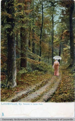 Woman in a full-length pink dress, carrying a white parasol, walks down a path through a woods. There are fallen leaves along and beside the path. Jacob's Park is now known as Iroquois Park. Dates to the turn of the 20th century.