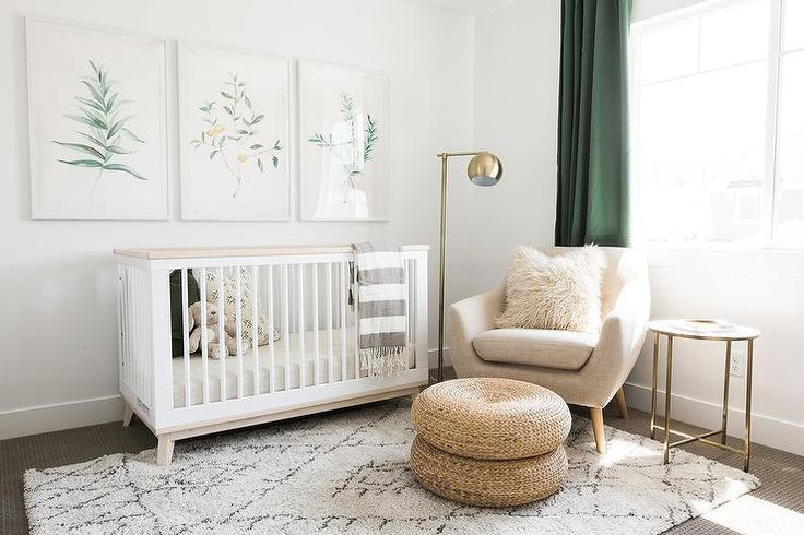 White and green nursery features three botanical prints placed over a Babyletto Scoot 3-in-1 Convertible Crib with Toddler Rail drape din a gray striped throw blanket placed atop a black and white Moroccan rug.