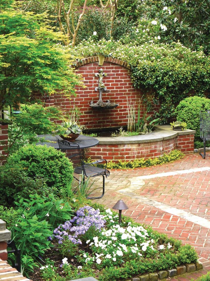 A brick fountain with an arched wall adds tons of charm to this lovely courtyard. Lush greenery and flowers lend privacy to the space, making the metal table and chairs extra inviting