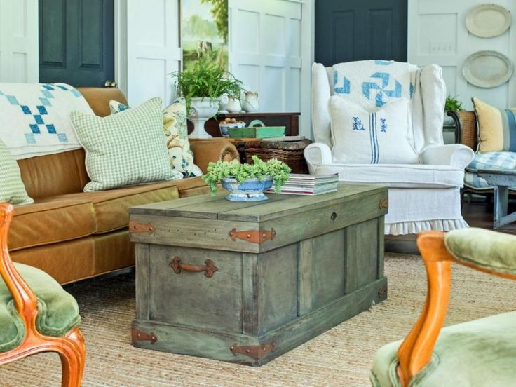 Living Room: Rustic Trunk Style Coffee Table. coffee table with storage. trunk coffee table. orange sofa. natural rug. green accent chair. upholstered rug. wooden coffee table. traditional living room.