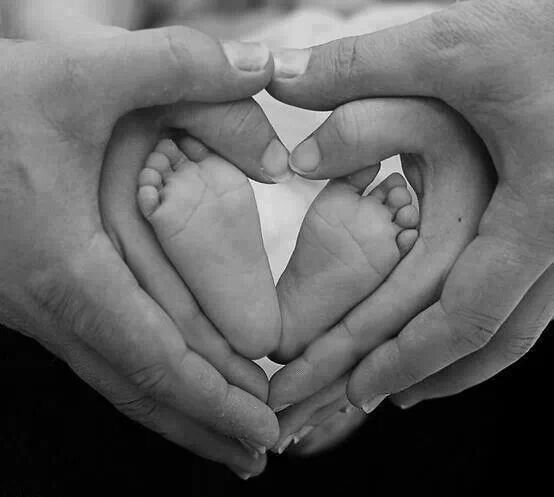 Newborn photo idea with both parents creating lovely hearts
