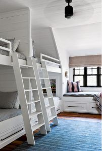 Side by Side Bunk Beds with Shiplap Trim. Bunk room features white ladders mounted on side by side built-in bunk beds accented with shiplap trim. Shiplap Bunk Room. Side by Side Bunk Beds with Shiplap Trim. Side by Side Bunk Beds with Shiplap Trim #Shiplap #Bunkroom #SidebySideBunkBeds #Shiplap #ShiplapTrim