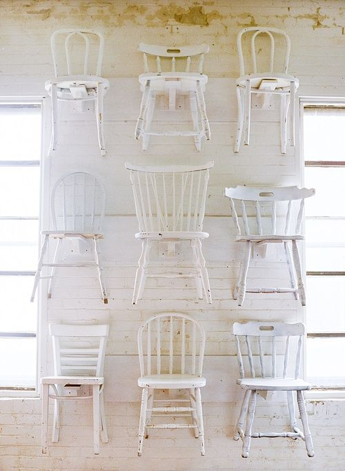 Our white wooden mismatched chairs displayed wonderfully on our showroom chair wall. So Pretty!