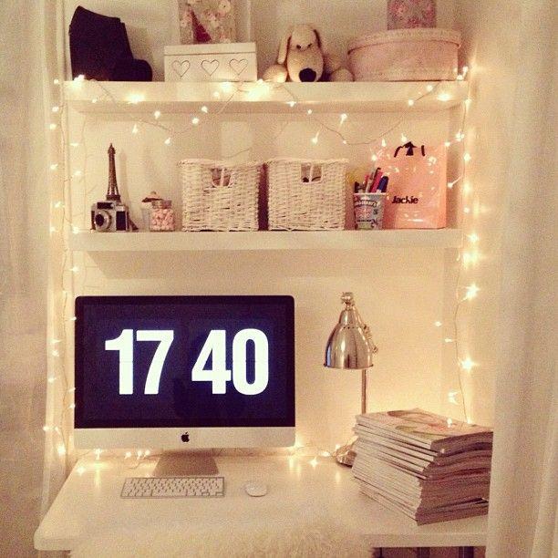twinkle lights on shelves. small desk area.