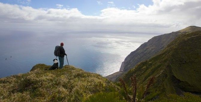 A Tristanian and his dog survey the vast South Atlantic Ocean from an island bluff.