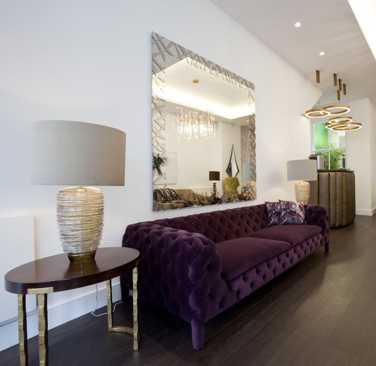 Purple chesterfield sofa with modern twist, beautiful table lamps, gorgeous gold legged end table, henge floating lights hanging over the coffee bar in our Great Portland Street showroom.