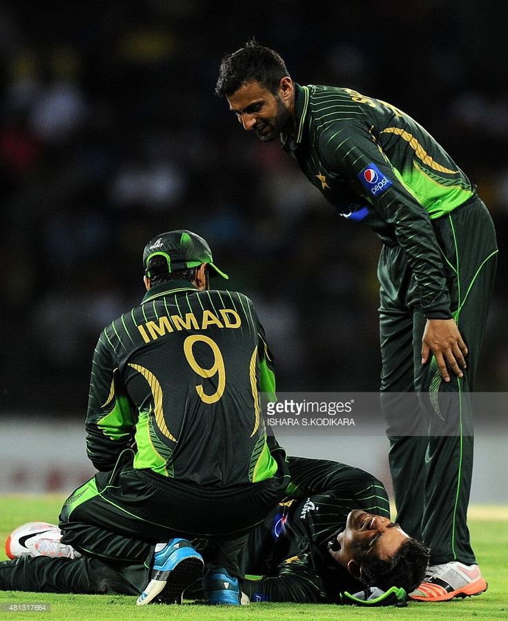 Pakistan cricket captain Azhar Ali (C) lays on the ground with a leg injury as teammates Immad Wasim (L) and Shoaib Malik (R) look on during the third one day international (ODI) cricket match between Sri Lanka and Pakistan at the R. Premadasa International Cricket Stadium in Colombo on July 19, 2015.