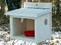 Coveside Post Mount Bluebird Feeder. Cleverly designed feeder allows small birds to dine while stopping larger birds. Center chamber with side openings allows birds to enter the piece and dine. Included, red cup can hold mealworms or berries. Front, plexiglass panel allows you to watch the avian activity. Flat back mounts to a post or tree easily.