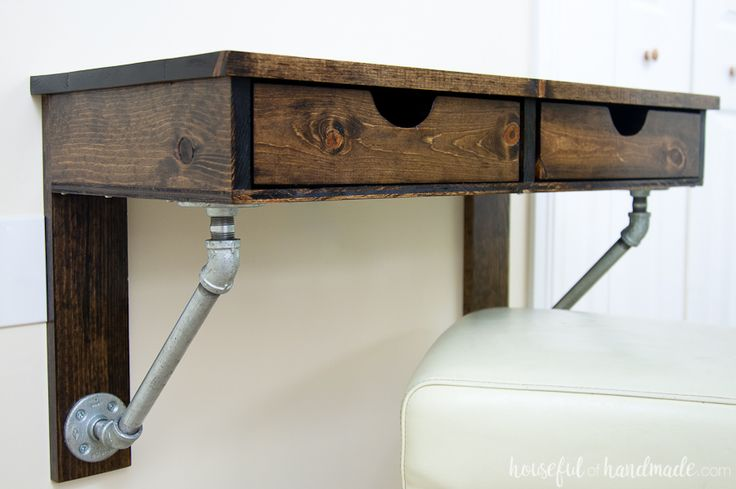 A wall-mounted desk perfect for small spaces or kids rooms. The desk is supported with galvanized plumbing pipe for an industrial accent. Includes two drawers perfect for office supplies.