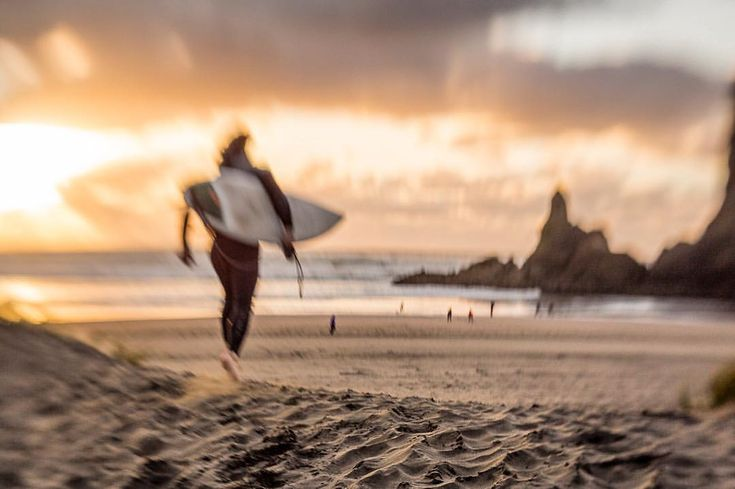 Surfer heading down to the water in Piha, NZ just before sunset. Board under arm. #movement #goldenhour #lionsrock #cloudyskies #earlyevening #kiwisummer