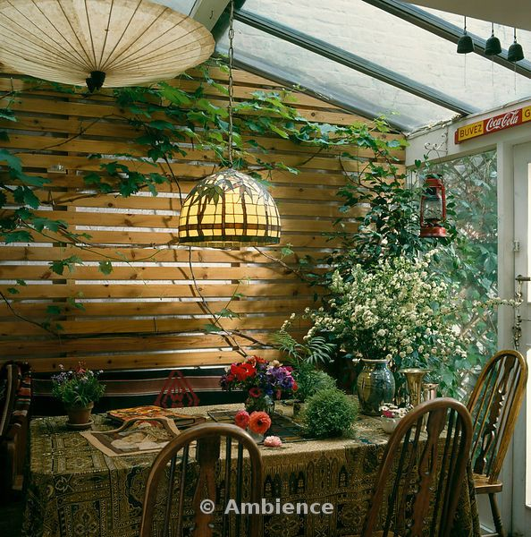 Ambience Images | Glass lampshade over wooden dining table in small conservatory extension with trellis panelling