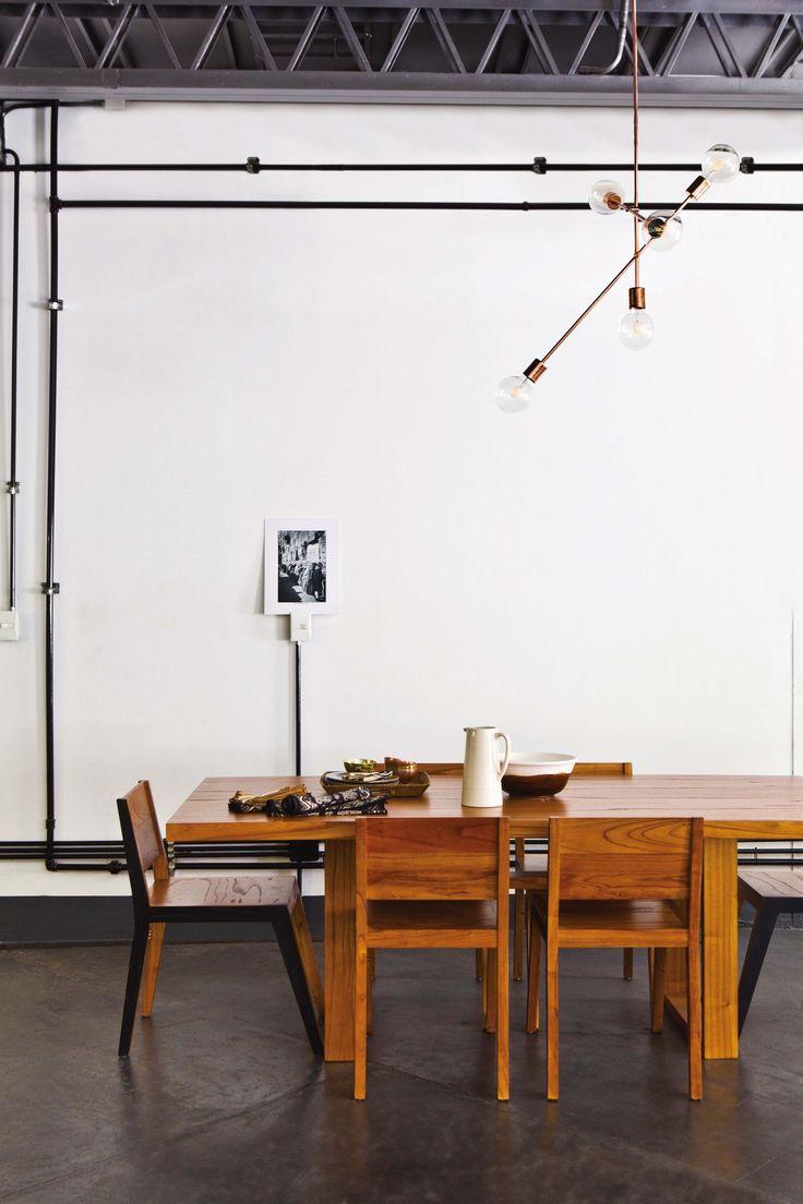Vista del comedor minimalista en el loft industrial de un diseñador de moda francés en Villa Crespo. Paredes blancas con prolija instalación eléctrica a la vista y lámpara geométrica con varios focos en distintos niveles.