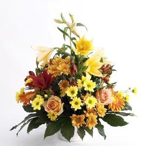 Un centro de flores cálido y clásico. Este centro de flores tiene rosas, gerberas, margaritas, y astromelias | Bourguignon Floristas