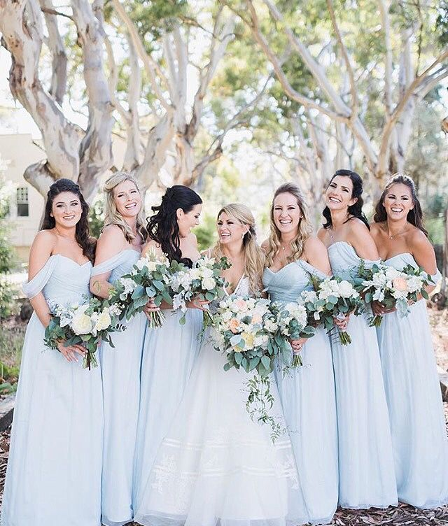Real bride Celeste chose pale powder blue dresses for her bridesmaids. The soft color palette is dreamy! Wedding dress: Sidney by Anne Barge.