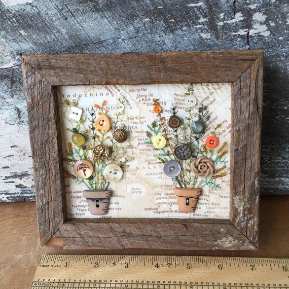 Cuadro en estilo rústico con botones en forma de maceta y botones clásicos de varios colores y modelos haciendo las veces de flores. Los tallos son bordados.
