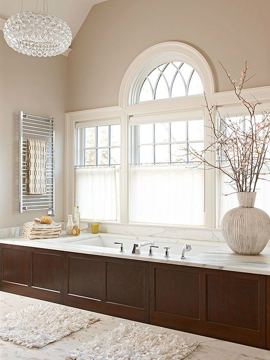 Brown tones bathe this traditional bathroom in warm and inviting character. Deep chocolate covers a wood-clad built-in bathtub, which blends seamlessly with lighter khaki-color walls. Creamy white emphasizes the architectural detail of surrounding windows./