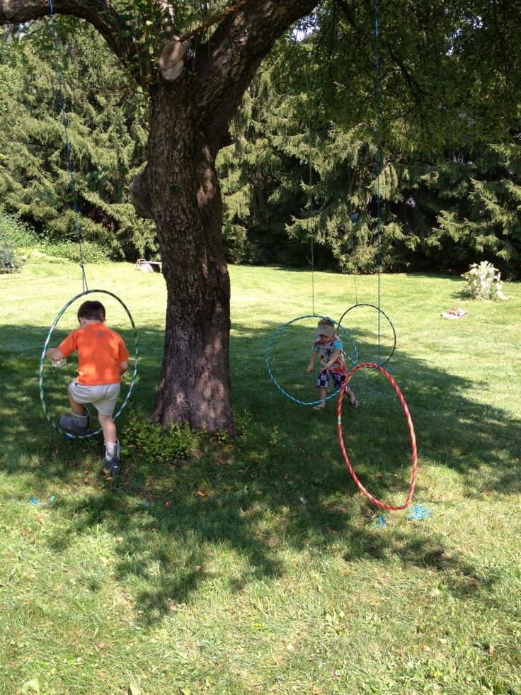 let the children play: love the hula hoops hanging from the large tree...spatial awareness