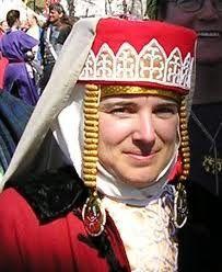 Volosnik: Tocado, tipo de diadema metálica adornada con piedras o cristal, fijados en un bonete llamado volosnik, usado en el traje tradicional ruso.