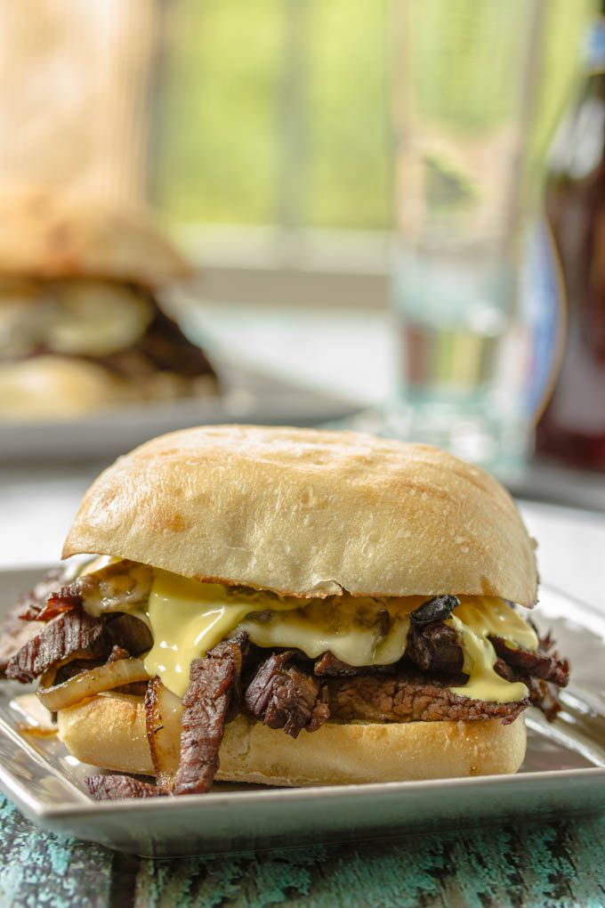 Man-friendly sandwiches made with thinly sliced, barbecued, and very tender flank steak, sweet caramelized onions, sauteed mushrooms, and creamy melted havarti cheese. #flanksteak #leftovers #steaksandwich