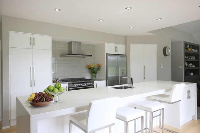 A light and bright kitchen bridges the lounge and dining rooms. Visitors to the home gather around the kitchen island to share a coffee and a catch up.