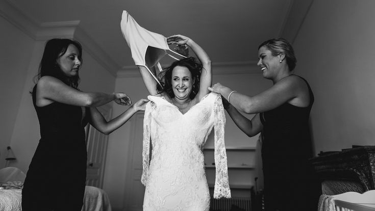 Bride wearing her wedding dress with the help of the bridesmaid