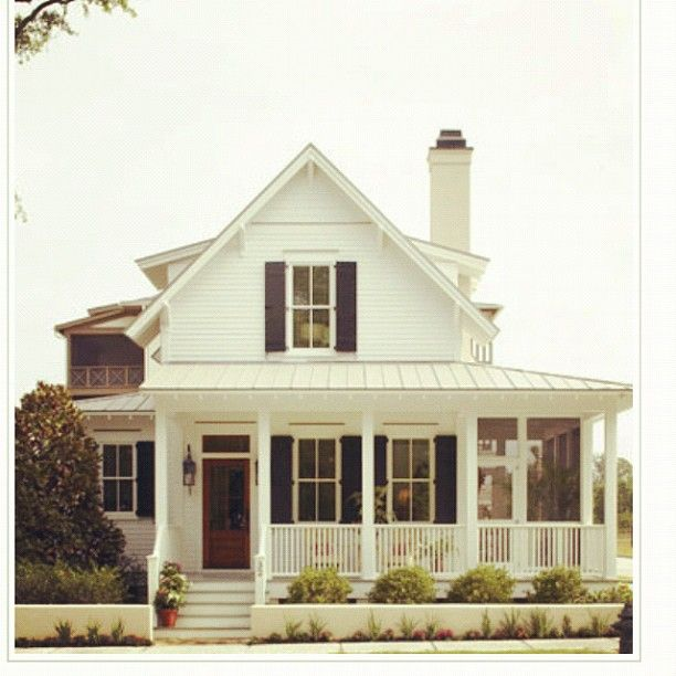 white farmhouse with wrap around porch   |