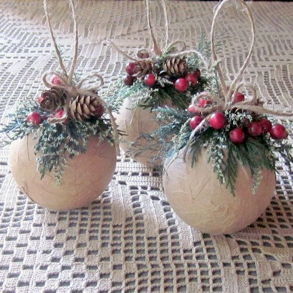 Christmas ornaments wrapped with brown paper and decorated with preserved cedar, wisps of caspia and red berries.