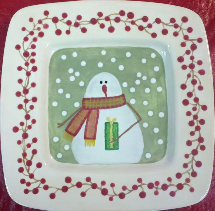 Snowman painted on a plate holding Christmas present. Holly berries around border. Snowflakes falling around snowman wearing scarf.