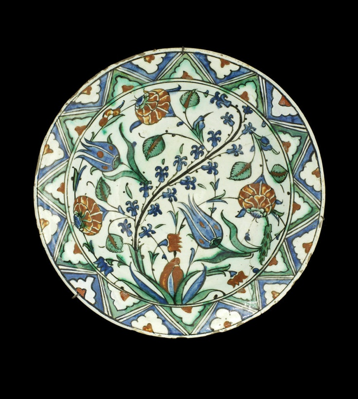 An Iznik pottery Dish   Turkey, 17th Century  decorated in polychrome on a white ground, depicting hyacinth, tulip and rose sprays emanating from a leafy stem, the border with triangular sections with a half flowerhead, verso with a frieze of abstract floral motifs