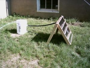 Solar Water Heater - Homemade solar water heater constructed from plywood, pond liner, a plastic bucket, hose, plexiglass, clamps, and wax paper.