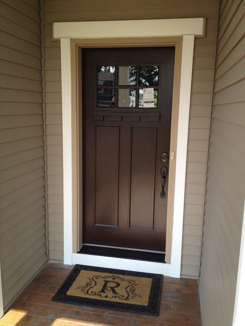 Beautiful brown door, dark hardware and   black door step