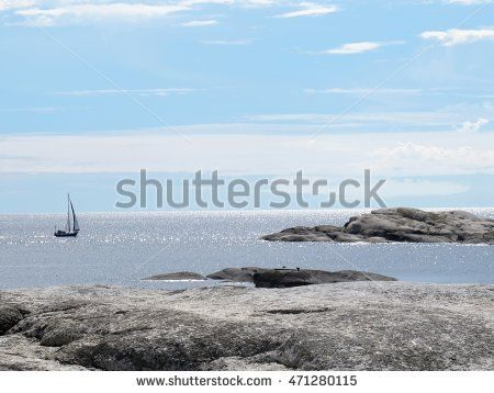 A sense of freedom. Beautiful sailboat sailing sail on the blue open sea spaces in Norway. Rocky shore in the foreground. Ocean horizon.