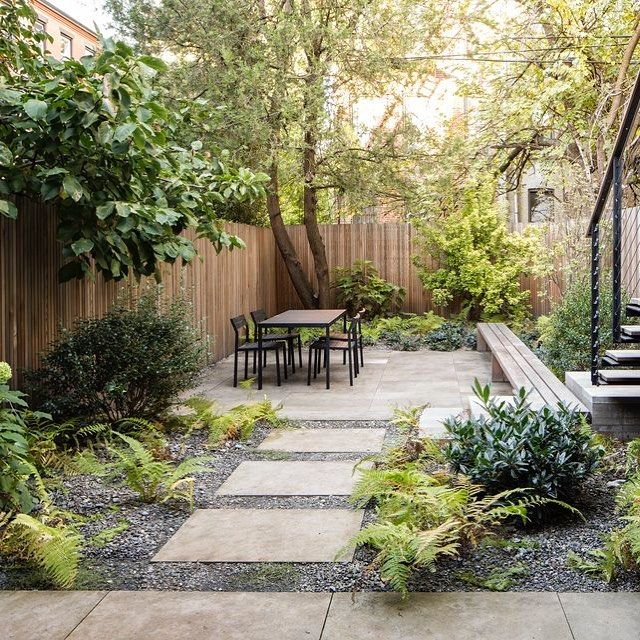"""In this Brooklyn backyard, @brooklandscape edged limestone pavers with crushed limestone dust mixed with gravel. """"It's a very modern look,"""" says the designer, """"but I tried to soften it with the gravel and plantings, like the ferns in the gravel."""""""