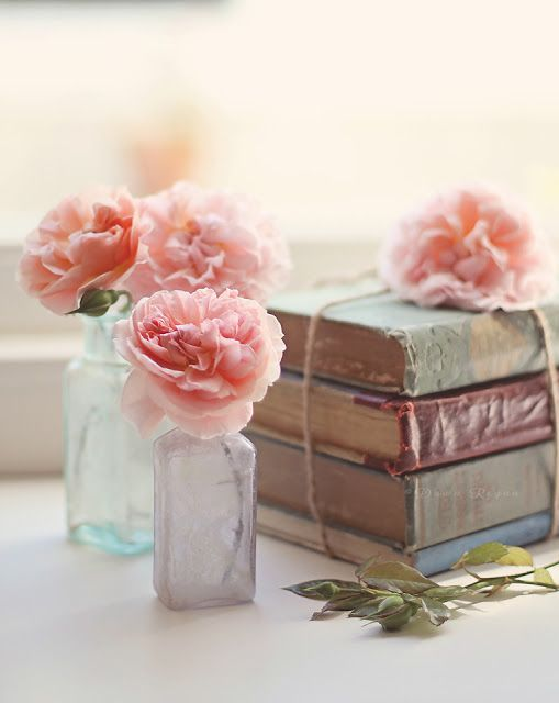Vintage books and colored bottles with flowers. Vintage decorating style.