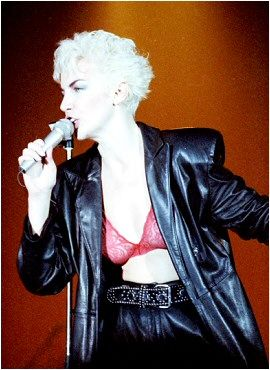 Scottish singer Annie Lennox of the Eurythmics in 1986. She is wearing high-waisted trousers, a black leather coat with a pink lace bra underneath.