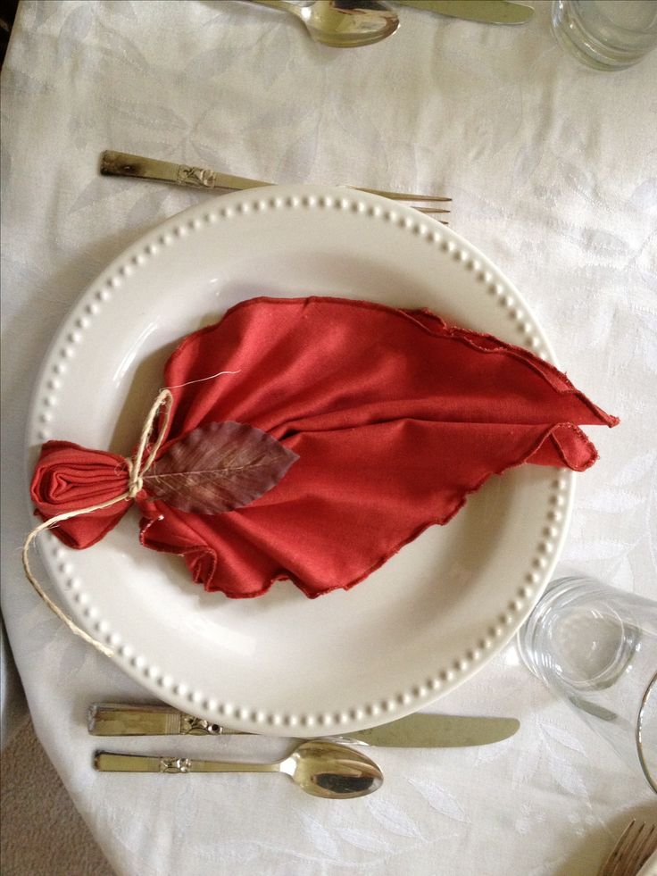 table setting with leaf napkins. (Fold napkin in half diagonally, accordion fold, fold in half again and pinch secure the bottom with twine.)