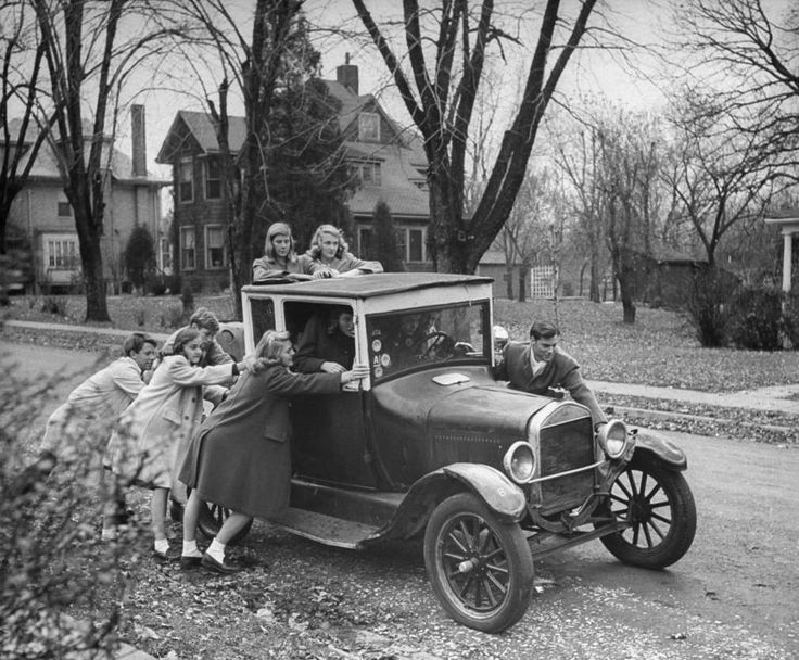 """In 1944, LIFE magazine introduced its readers to a strange new breed of American citizen: the """"teenager"""" -- specifically, teenage girls -- who would shape Western culture and commerce for decades to come. Gang of teen-agers push boyfriend's model T to get it started. Car is 17 years old and can hold 12 boys and girls. Favorite ride is out to football game."""