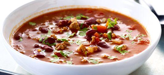 (ingrediënten voor 4 à 6 personen)      Verwarm de olie in een stoofpot. Bak er de gehakte ui en het rundergehakt in aan. Roer en breek het vlees in kleine stukjes met behulp van een spatel.     Voeg, wanneer alles mooi bruingebakken is, het geperste knoflookteentje en de specerijen toe, meng 1 min., doe er de gepelde tomaten bij. Vul het lege blik met warm water en voeg het water toe aan de bereiding. Doe dit 3 x. Doe er de verkruimelde bouillonblokjes en de tomatenpuree...
