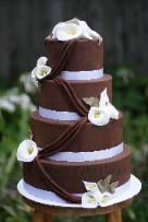 4 tier round chocolate brown wedding cake with white calla lilies... I love the idea of the icing drooping across to the other flowers, but not a fan of the brown