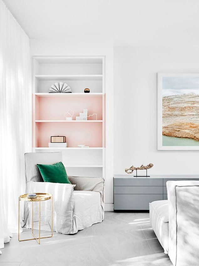 White living room with pale pink bookshelves - pop of color