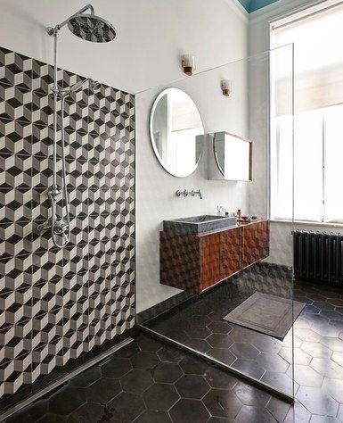 In the bath, tumbling blocks–patterned tile makes a statement in the shower, as does a jolt of blue overhead. A floating cabinet by Danish designer Kai Kristiansen adds a midcentury touch | archdigest.com
