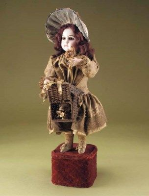 A bébé Niche automaton by Lambert,  with Jumeau bisque head, closed mouth, fixed brown paperweight eyes, arched brows, pierced ears with earrings, brown mohair wig, bisque hands holding flowers and a wicker basket, on velvet-covered base with going-barrel movement playing one air and causing the figure to turn and nod her head and lift the basket lid to reveal a nodding dog, in original figured olive satin jacket, slippers and knee-length pleated skirt trimmed with lace and ribbons -- 19in…