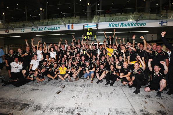 Kimi Raikkonen of Finland and Lotus celebrates with team mates in the pitlane after winning the Abu Dhabi Formula One Grand Prix