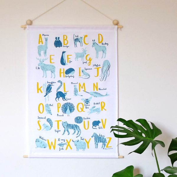 Stephanie Cole Design A-Z Animals Wall Hanging: For small kids to 'big kids' a-like, this new wall hanging by talented UK based illustrator Stephanie Cole, is inspired by modern, Scandinavian design and will carry a room through all stages of nursery to adult life with a design conscious nod to learning and decor. Screen printed with environmentally friendly ink in aqua, teal and yellow onto white cotton fabric. Hemmed on each side and hung on two natural wooden poles. Matching wooden beads…